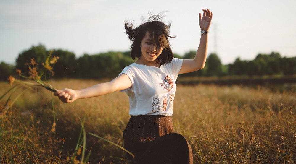 woman running in a field to keep a healthy lifestyle
